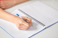 hands of student girl with pen writing to notebook