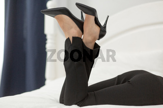 Legs of businesswoman laying on bed. Attractive legs of woman laying on bed wearing black pants and black stilettos with pointed toe. Close up shot