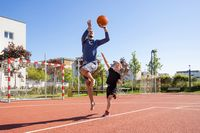 Father and son playing basketball barefoot on a playground