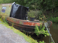 an old rusting houseboat overgrown with weeds moored on the rochdale canal listing to one side and beginning to sink