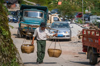 Chinese man carrying heavy load