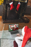 Rear view of woman in santa hat having a videocall with senior couple in santa hats smiling on lapto