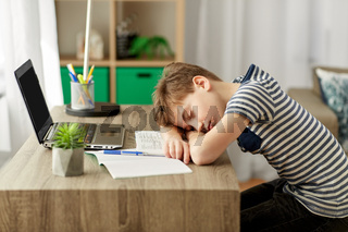 tired student boy sleeping on desk at home