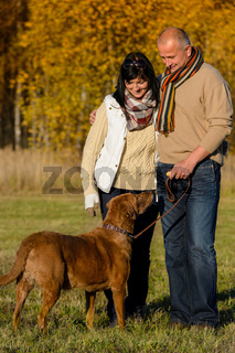 Couple with dog in sunny autumn park