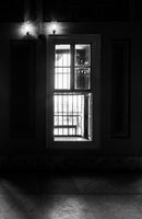 Black and white of narrow windows, revealing strong light into dark room with tiled marble floor