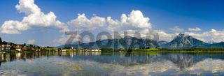 panorama landscape with lake Hopfensee in Bavaria at sunny summer day with alps mountains