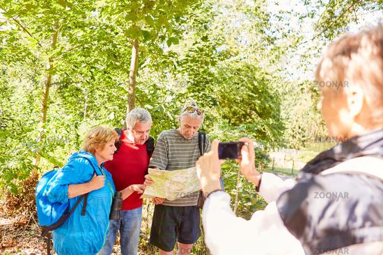 Seniorin fotografiert eine Senioren Wandergruppe