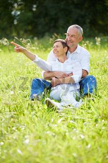 Senioren sitzen im Gras und Frau zeigt mit Finger