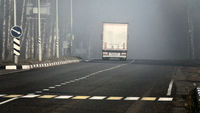 Truck on highway in bad winter weather with heavy fog.