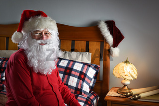 Closeup of Santa Claus wearing a red union suit sitting on the edge of his bed at the North Pole, ready to go to sleep after delivering packages on Christmas eve.