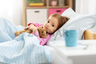 sick little girl lying in bed at home