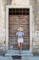 Beautiful young female tourist woman standing in front of vinatage wooden window and textured stone wall at old Mediterranean town, smiling, holding, using smart phone to network on vacationes