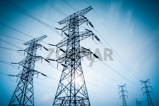 high voltage electricity transmission pylon silhouetted