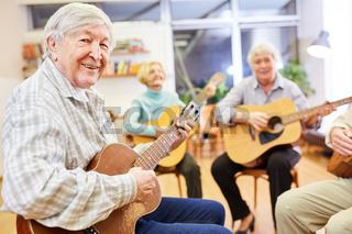Fröhlicher Senior Mann spielt Gitarre in einem Gitarrenkurs der Volkshochschule