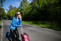 A teenager is standing with a pink suitcase on wheels and tries to stop the opportunity to go on vacation faster.