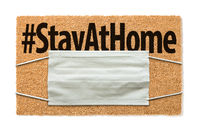 Welcome Mat With Medical Face Mask and #Stay At Home Text Isolated on White Amidst The Coronavirus Pandemic