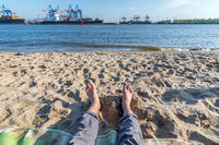 Relaxing at the beach at the Elbe river in Hamburg with harbour facilities and container vessels in the background