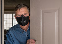 Senior man with face mask peering through front door for visitors during quarantine