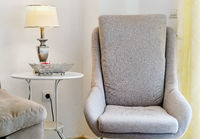 Grey colour modern cozy arm chair inside of light pretty living room