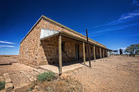 Australia – Outback desert with an old abandoned vintage railway station near the old Ghan under blue sky
