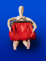 Wooden toy figure with red purse on blue