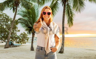 woman on beach showing thumbs up