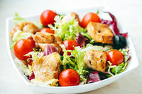 Chicken salad with cherry tomatoes, lettuce and veggies for healthy diet, food delivery service and order online