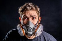 A man in a respirator mask with an increased degree of protection against harmful environmental factors. Half face mask. Isolate Virus fear concept.