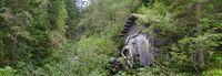 Alte ehemalige hölzerne Mühle mit Wasserrad in einem dichten Wald in Osttirol