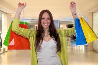 Junge Frau mit Einkaufstaschen hat Spaß beim Einkaufen in Shopping Mall