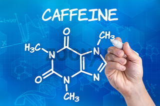 hand with pen drawing the chemical formula of Caffeine