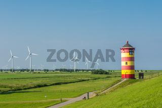Leuchtturm Pilsum mit Windturbinen an der deutschen Nordseeküste, Ostfriesland, Deutschland