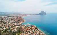 Aerial photography panoramic image Calpe or Calp townscape rooftops picturesque view bright Mediterranean Sea waters and Parque natural Penon de Ifach or Penyal de Ifac rock, Costa Blanca, Spain
