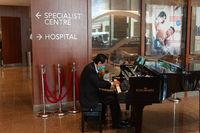 Singapur, Republik Singapur, Ein Pianist mit Mundschutz spielt im Foyer eines Krankenhauses Fluegel
