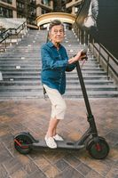 90 year old woman with gray hair, wrinkles, progressive and active uses modern electric transport scooter. Lady pensioner use eco friendly city vehicle. Senior female using urban personal transport
