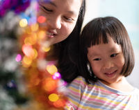 Little asian girl with mom decorating a Christmas tree together