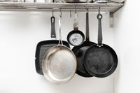 Various pans in different sizes and forms for cooking and frying hanging on metal hooks from shelf in kitchen with white wall in background
