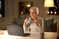 senior woman with laptop drinking coffee at home