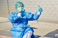 Mediziner oder Containment Scout in Schutzkleidung zeigt Daumen hoch