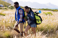 Fit afrcan american couple wearing backpacks nordic walking with poles in mountain countryside