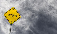 Yellow covid-19 sign with cloudy background