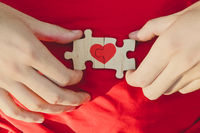 Red heart is drawn on the pieces of the puzzle in male hands on red background. Love concept. St. Valentine day