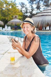 Seniorin im Pool mit Tablet Computer liest Ebook