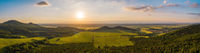 Summer nature scenery at sunset with green forests and meadow and blue sky