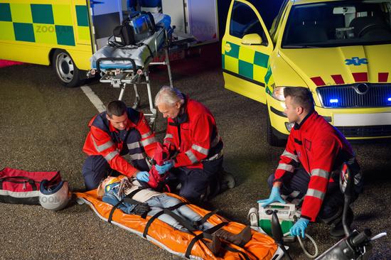 Paramedics helping motorbike driver on stretcher