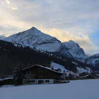 Sun lit clouds behind the peaks of Mount Spitzhorn and Arpelistock.