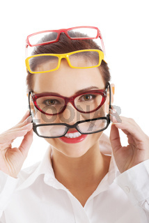 Beautiful woman wearing four different pairs of eyeglasses.