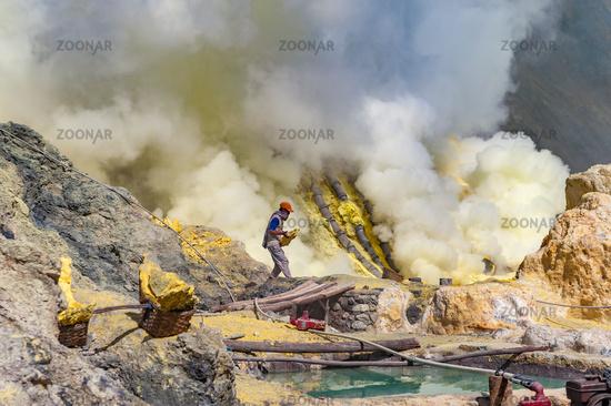 Kawah Ijen, Java, Indonesia - August 6, 2010: Sulfur miner carrying sulfur block at Kawah Ijen volcano in East Java, Indonesia.