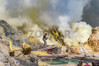 Kawah Ijen, Java, Indonesia - August 6, 2010: Sulfur miner carrying sulfur block at Kawah Ijen volcano in East Java, Indonesia.
