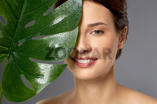 beautiful young woman with green monstera leaf